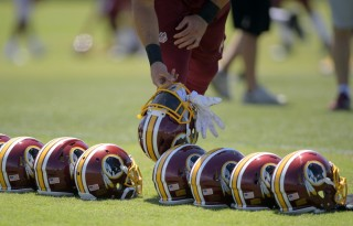 Players retrieve helmets after doing stretch exercises during the first day of the Washington Redskins mini camp at Redskins Park in Ashburn on June 14. (John McDonnell/The Washington Post)